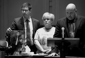 WILLIAM, RIGHT, AND SUSAN GARLAND address the courtroom in Androscoggin County Superior Court in Auburn Tuesday. The Garland's son, Connor, was with his girlfriend, Cassidy Charett, on the night that Charett died during a hayride crash at Harvest Hill Farm on Oct. 11, 2014. Attorney Alexander Spadinger holds a picture of Connor Garland and Charett.