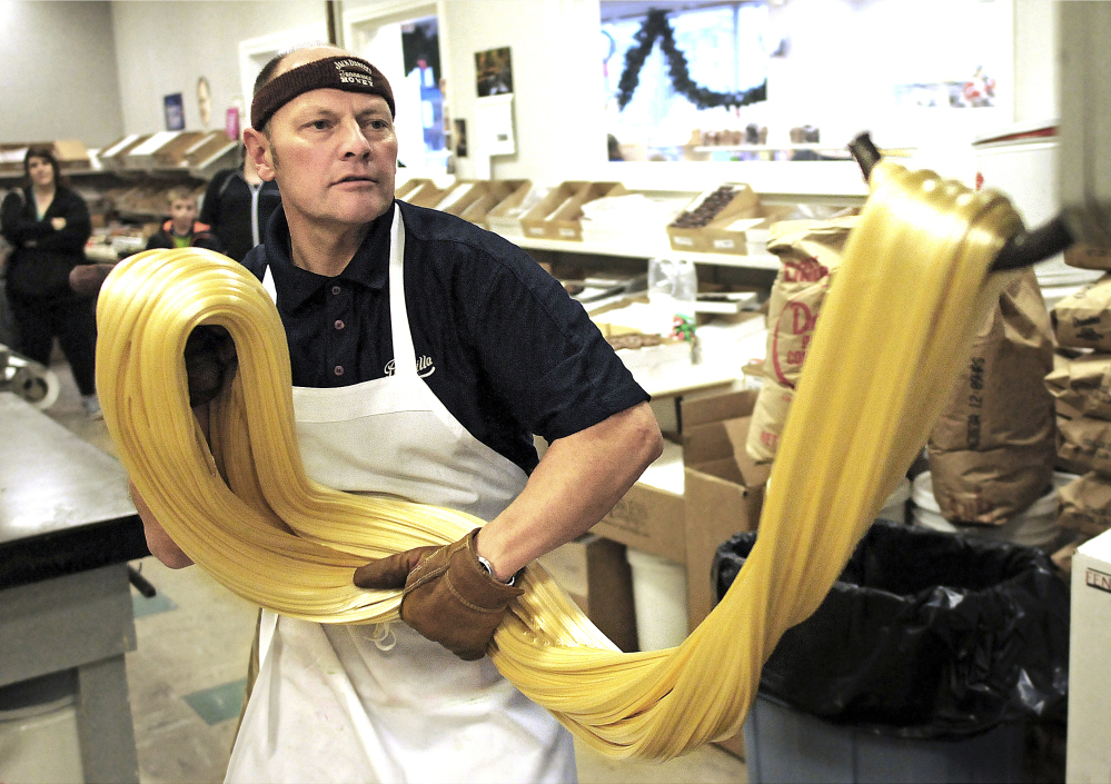 Priscilla Candy Shop owner James Gallant stretches out a batch of candy cane mix at the store in Gardner, Mass. Workers prepare them each year right after Thanksgiving. Gallant said he has made about 50,000 candy canes since he joined the business 31 years ago.