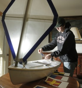 Seven classmates in Kennebunk High School's Alternative Education program joined with a land trust and The Landing School to build a 5-foot boat that will depart from coastal Maine and steer itself across the Atlantic. Senior David Patoine, above, puts a sticker on the boat, which will be launched about 150 miles offshore.