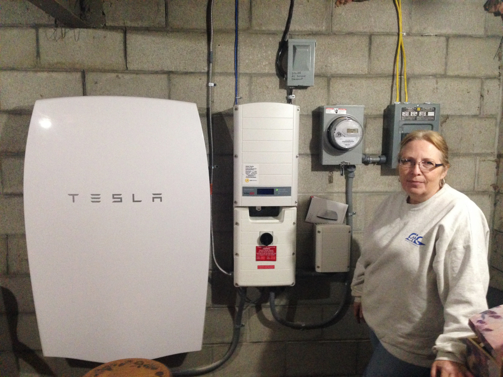 "Associated Press/Dave Gram Rhonda ""Honey"" Phillips  of Middletown Springs is one of the growing number of Green Mountain Power customers using the Tesla battery to store solar energy when her panels aren't collecting it."