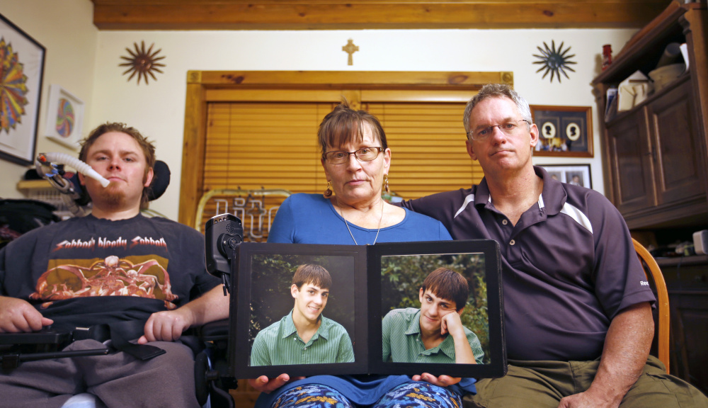 """The Norton family is mourning """"JT"""" Norton, who had schizophrenia. From left are brother Michael, mother Suzan – holding a photo of JT when he was younger – and father Terrence."""