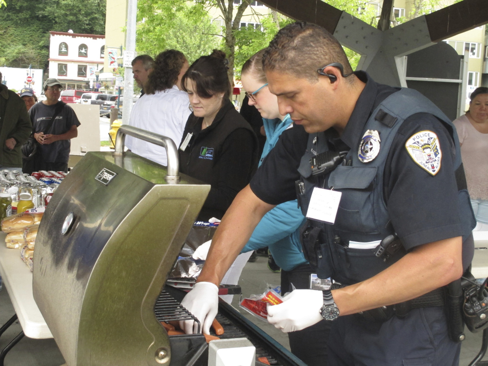 Juneau Police Officer Ken Colon grills hot dogs last July during a gathering sponsored by the police department to let people take a stand against violence.