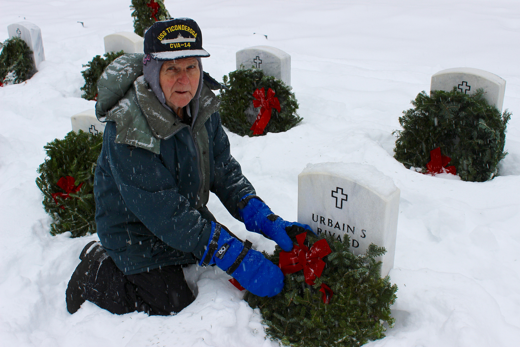 Veteran Ron Rivard places a wreath against his brother Urbain's gravestone. Dozens showed up to the Southern Maine Veteran's Cemetery in Springvale to pay their respects at the Wreaths Across America event Saturday. RYDER SCHUMACHER/Journal Tribune
