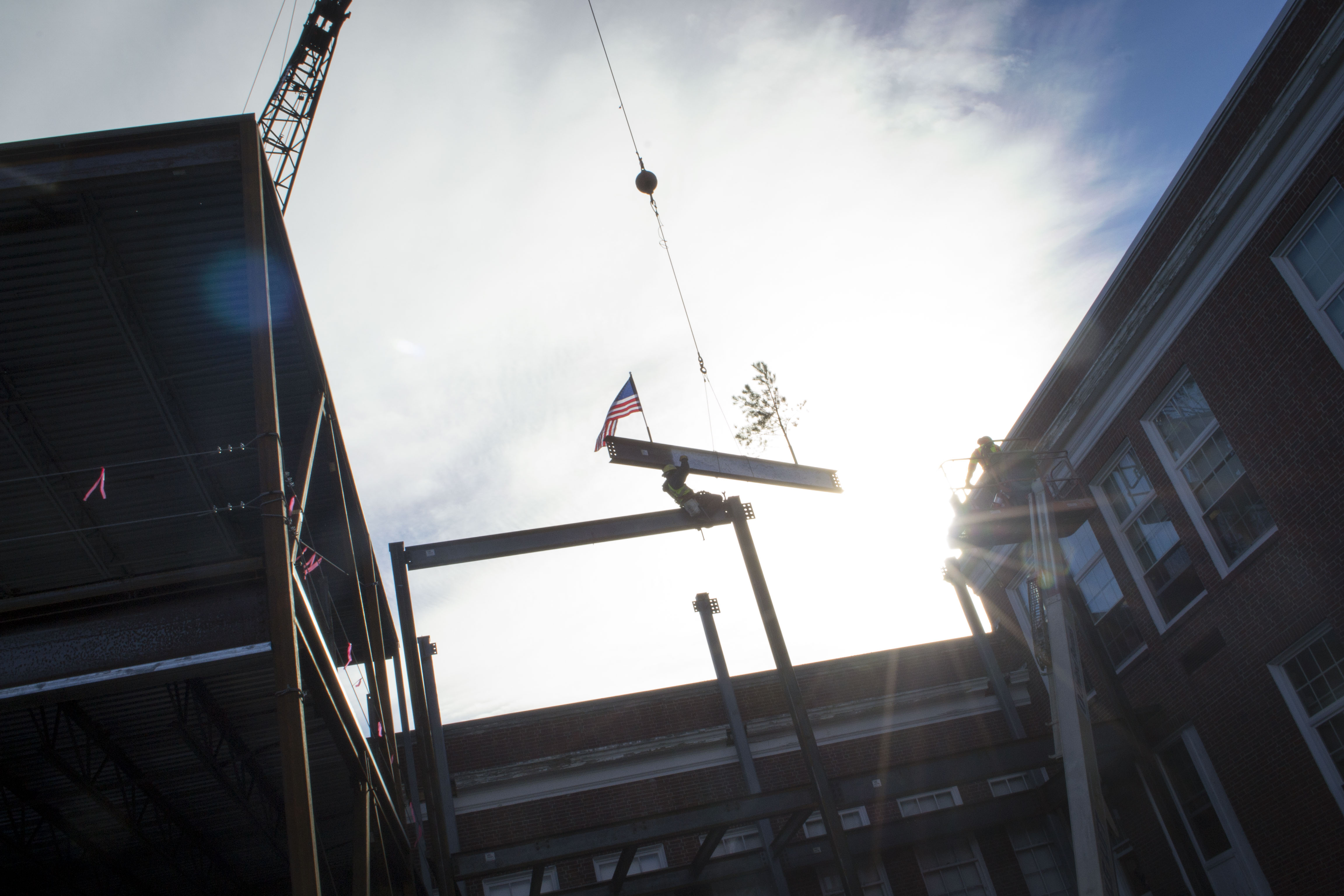 ALAN BENNETT/Journal TribuneA construction worker assists in placing the final steel beam of a multimillion dollar renovation at Kennebunk High School on Friday. The tree noticeable on the right is an ancient construction tradition marking the placement of a building's highest structural element, it's most