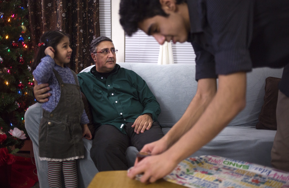 Abdullah Ali, 16, serves tea to his father, Ahmed Ali, seated with his daughter Fatimas, 6, at their apartment in Westbrook. After police met with residents about anti-Muslim messages left at the complex, many of his neighbors and friends felt reassured, Ali said.