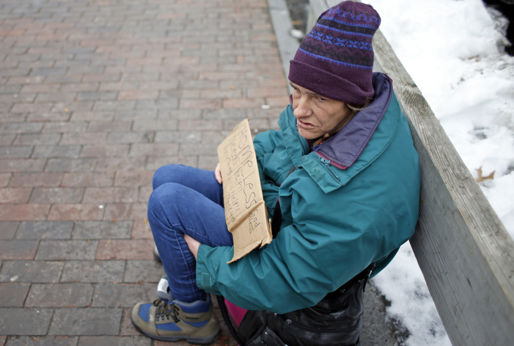 "Michelle Brooks panhandles on Commercial Street, holding a sign that reads, ""Homeless. Needs Help. Anything helps. God bless."" The practice is a growing concern in many cities."