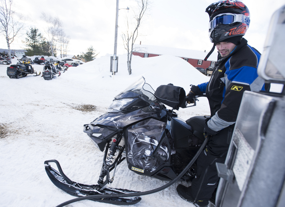 Ryan Kelly, of Cumberland, Rhode Island, gasses up at Shin Pond Village. The outfit is renting snowmobiles again for the first time in years and is exploring expansion to serve four-season clientele.