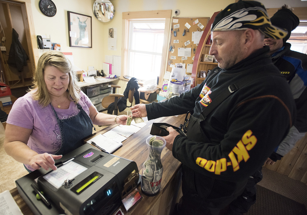 Proprietor Terry Hill waits on snowmobilers as they gas up their machines and eat at her family's restaurant at Shin Pond Village in the Penobscot County town of Mount Chase last week. Hill was originally opposed to the creation of the Katahdin Woods and Waters National Monument, but has come to embrace its positive effects on business.