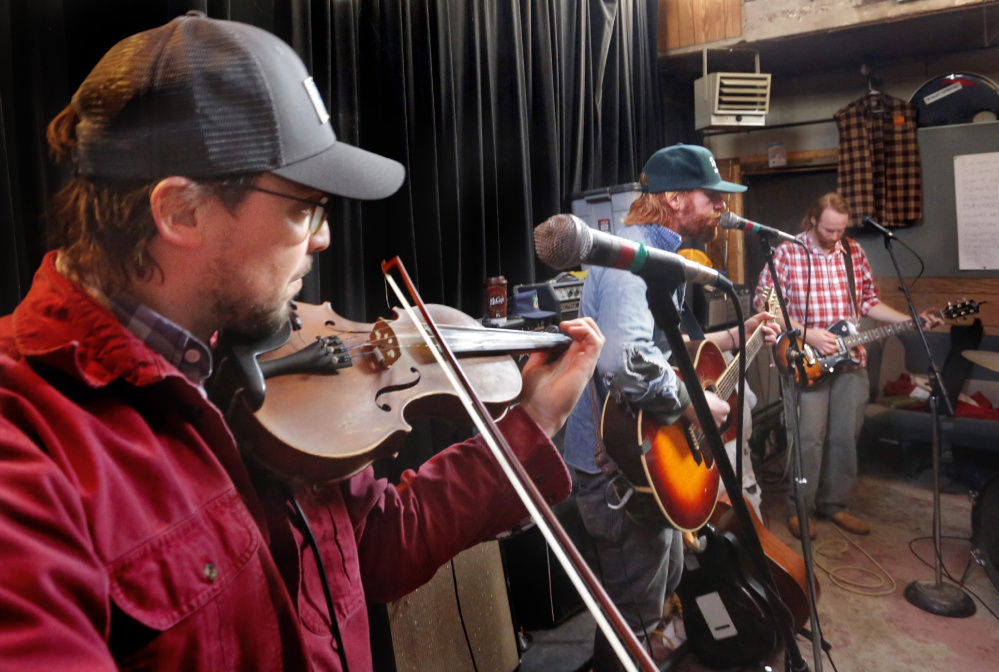 """From left, Andrew Martelle, Will Mallett and Luke Mallett of The Mallett Brothers Band rehearse songs from their new album """"The Falling of the Pine: Songs from the Maine Woods"""" at a Portland rehearsal studio on Jan. 9."""