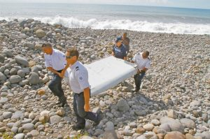 """FRENCH POLICE OFFICERS carry a piece of debris from a plane known as a """"flaperon"""" on the shore of Saint-Andre, Reunion Island, in 2015. While search crews spent years trawling in futility through a remote patch of the Indian Ocean for the missing Malaysia Airlines Flight 370, people wandering along beaches on the other side of the ocean began spotting debris that washed ashore. Those pieces provided key information and raised questions whether Malaysia, Australia and China - who funded the hunt for the underwater wreckage - missed key opportunities by failing to organize coastal searches for plane parts."""