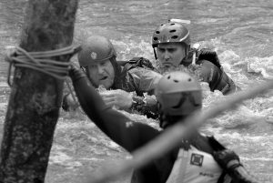 JASON WILLIAMS, left, is rescued by Calfire rescue swimmer Danny Ciecek after Williams got snagged on trees while trying to kayak the Carmel River with a friend near Paso Hondo Road in Carmel Valley on Monday.