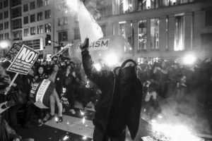 PROTESTERS BURN SIGNS outside the National Press Building ahead of the presidential inauguration Thursday in Washington.