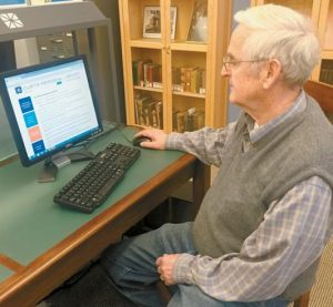 RICHARD F. SNOW browses through the Snow Index in the Genealogy and Local History Room at Curtis Memorial Library.