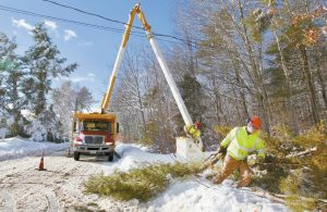 BRIAN MURRAY of Lucas Tree Experts hauls away giant tree branches cut by Don Libby as they clean up limbs and debris causing downed wires along Wood Road Friday in Gorham. Nearby residents are without power as a result of the heavy wet snow that fell overnight.