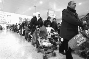 ABOVE, THE ALAHAMAD family waits at Athens International Airport for their flight to France with other refugee families. Abd Alwahab Alahamad, his wife Iman Mshanati and children, 5-year-old Nora, 2-year-old Ahmed and baby Layan, 6 months, were among the lucky few accepted so far into a European relocation program. Like hundreds of thousands before them, the Alahamads risked everything to escape war and the dark brutality of the Islamic State group.