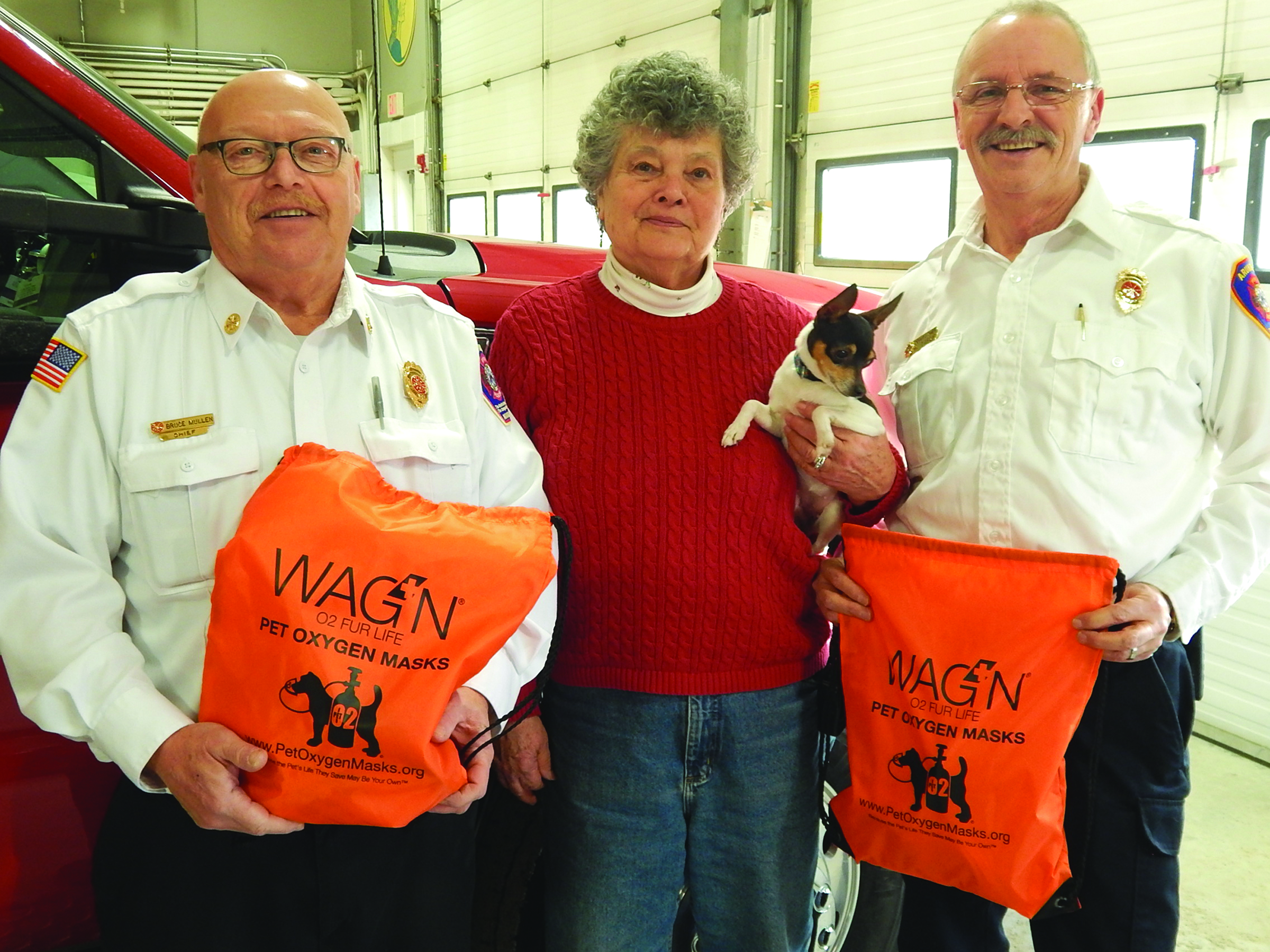 The York County Kennel Club has donated two pet mask oxygen systems to Arundel Fire-Rescue in an effort to  help firefighters save the lives of pets. From left are Arundel Fire-Rescue Chief Bruce Mullen, York County Kennel President Sandy Bergeron, 2-year-old Toy Terrier Solo and Arundel Deputy Fire-Rescue Chief Renald Tardif. ED PIERCE/Journal Tribune