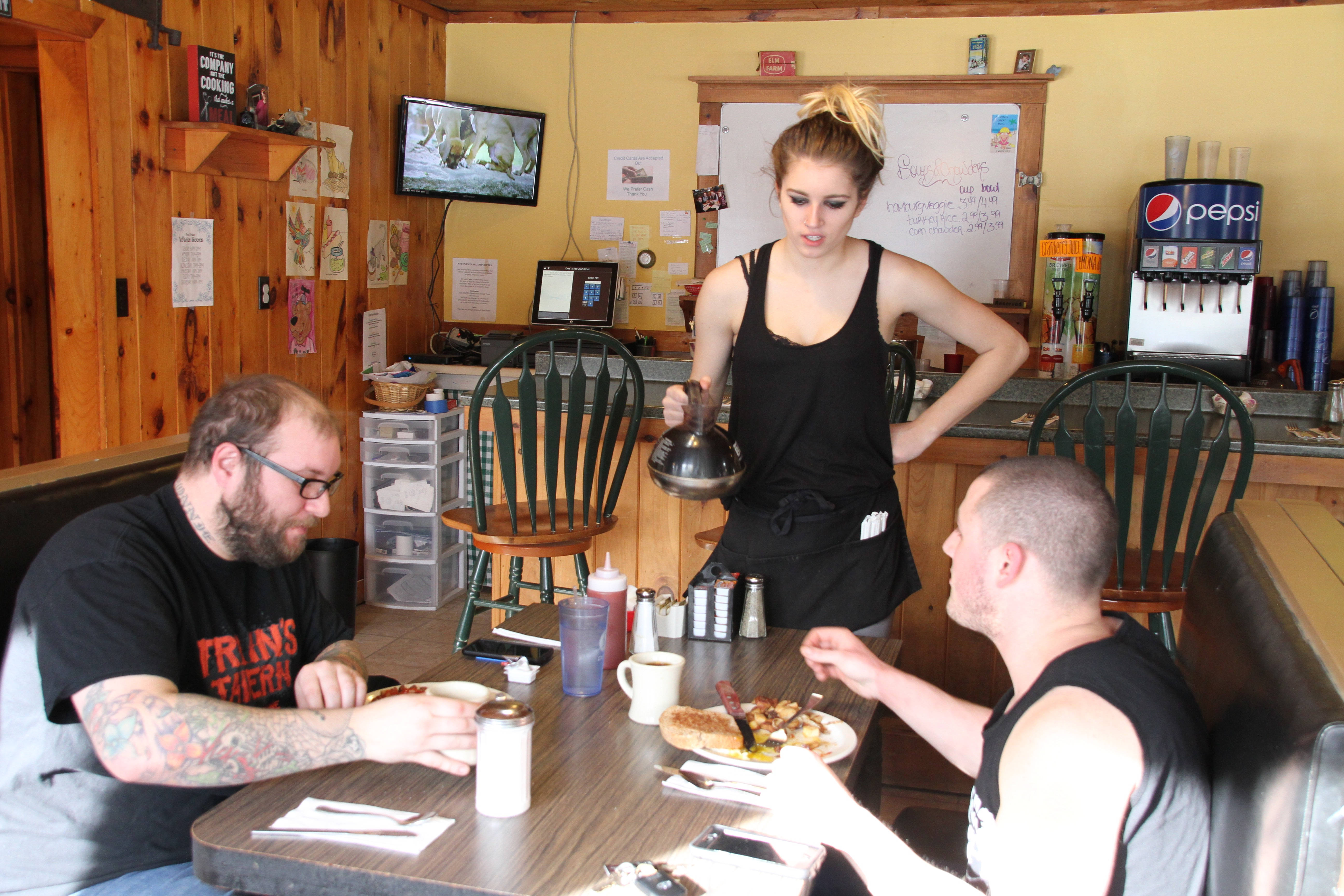 Olivia Tasker pours coffee for R.J. Soucie, left, and Nick McCrfisson, right, at Dee's Route 202 Diner in Lebanon Tuesday morning. Owner Stephanie Harding said  Maine's new minimum wage laws, approved by voters in a referendum Nov. 8, has meant she's had to lay off one employee, cut the hours of two others and reduce the diner's evening schedule from three nights to one for the winter months. The diner is open seven days a week for breakfast and lunch. TAMMY WELLS/Journal Tribune