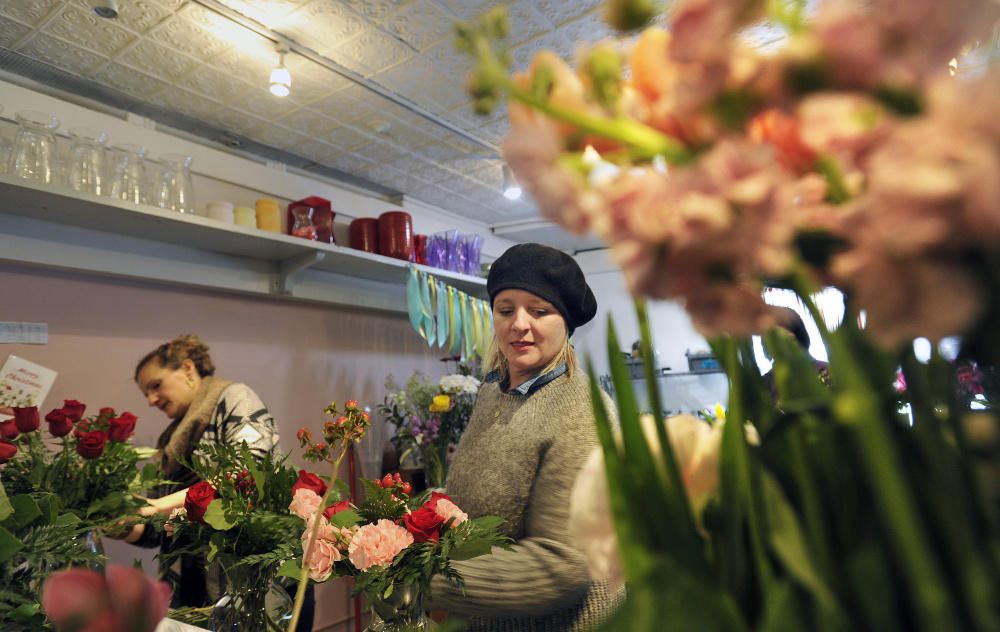 Staff photo by Shawn Patrick Ouellette Designers Jennifer Miller, right, and Anne Heelan put together floral arrangements Monday at Harmon's & Barton's in preparation for Valentine's Day.