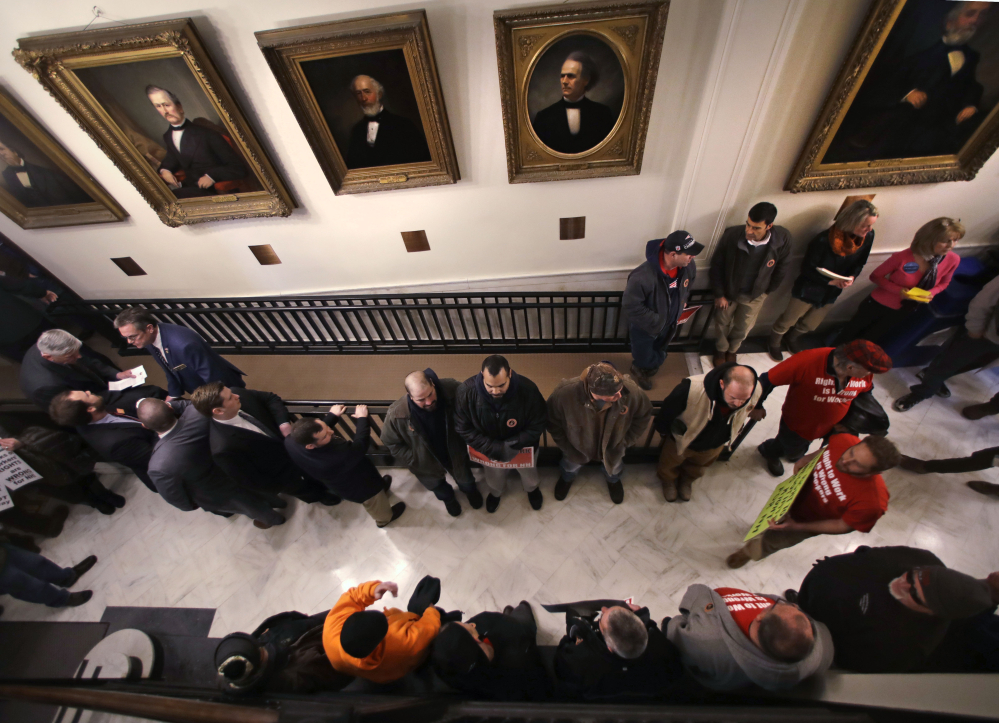 """Members of the Workers International Union of Bricklayers and Allied Craftworkers Local 3 protest Thursday outside the House Chamber in Concord, N.H., in advance of voting that rejected """"right-to-work"""" legislation, a defeat for Republican Gov. Chris Sununu."""