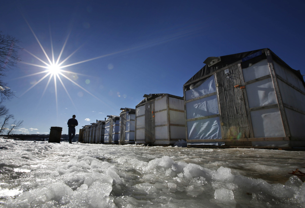 Tom Cowper of Peabody, Mass., walks from his ice fishing shack at Jim Worthing's Smelt Camp on the Kennebec River in Pittston while smelting in 2013. Fishermen and state regulators say the population of smelt appears to have made a comeback in 2017 after a down year in which few of them were caught.