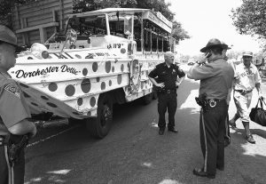 """IN THIS July 16, 2010, photo, police officers work the site of a crash involving an amphibious duck boat in Boston as the driver, right, identified only by his stage name """"Shoeless Joe,"""" departs the scene. State police said people were treated for minor injuries after the duck boat crashed into several cars on a Boston highway."""