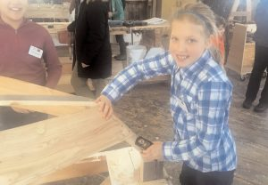 WEST BATH SCHOOL fifth-grader Campbell Jacobs sands the bow of one of the two boats the class is building in Maine Maritime Museum's Discovery Boatbuilding program.