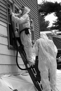KEITH DILL, left, and Chris Bowden from Renovate Right Construction, an EPA-certified safe lead-removal company, scrape lead paint on a Sabattus house and vacuum it with a HEPA vacuum. A Lewiston lawmaker has introduced a bill that would require renovators working on older homes to have at least one person certified in how to safely remove lead paint, including using the systems shown here.