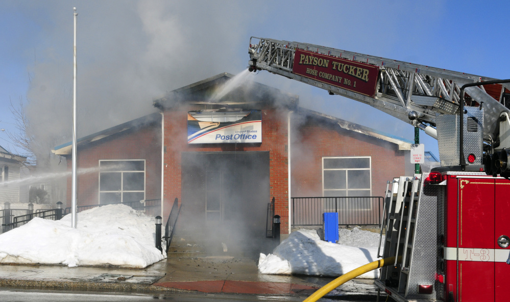 Firefighters work on Feb. 21 at the post office in Winthrop, which was destroyed by an accidental fire.