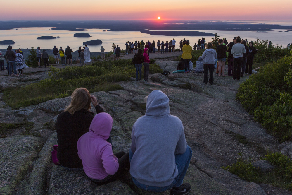 Hundreds of people gather atop Cadillac Mountain in Acadia National Park to watch the sun rise in June. The park's 100th anniversary contributed to Maine's jump in tourism in 2016.