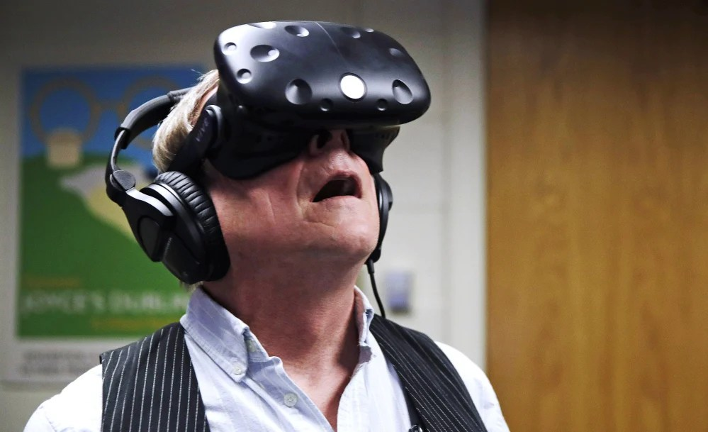 "Joseph Nugent, a Boston College English professor, wears virtual reality goggles at the school's virtual reality lab in Boston. College students in Boston are developing a virtual reality game based on James Joyce's ponderous tome ""Ulysses."" Nugent says the goal of ""Joycestick"" is to expose new audiences to the works of one of Ireland's most celebrated authors and to give a glimpse of how virtual reality can be used to enhance literature."