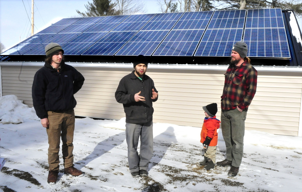 From left, Insource Renewables worker Ben Holt; Joas Hochstetler, manager of Backyard Buildings; and Matt Wagner, project manager for Insource, with his son, Ansel. Backyard Buildings makes solar-power sheds with Maine-based materials.