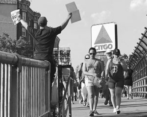 IN THIS JUNE 1, 2016, photo, a hawker sells programs with the iconic Citgo sign in the background as fans walk from Kenmore Square to a baseball game at Fenway Park in Boston.