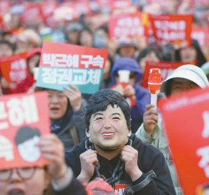 "A PROTESTER WEARING A MASK of ousted South Korean President Park Geun-hye attends a rally calling for her arrest in Seoul, South Korea. Media reports say that South Korean prosecutors have decided to ask a court issue a warrant to arrest former President Park on corruption allegations. Yonhap news agency reported Monday, March 27 2017, that prosecutors reached the decision after they grilled Park last week over suspicions she colluded with a jailed confidante to extort from companies and allowed the friend to secretly interfere with state affairs. The signs read: ""Park Geun-hye's arrest."""