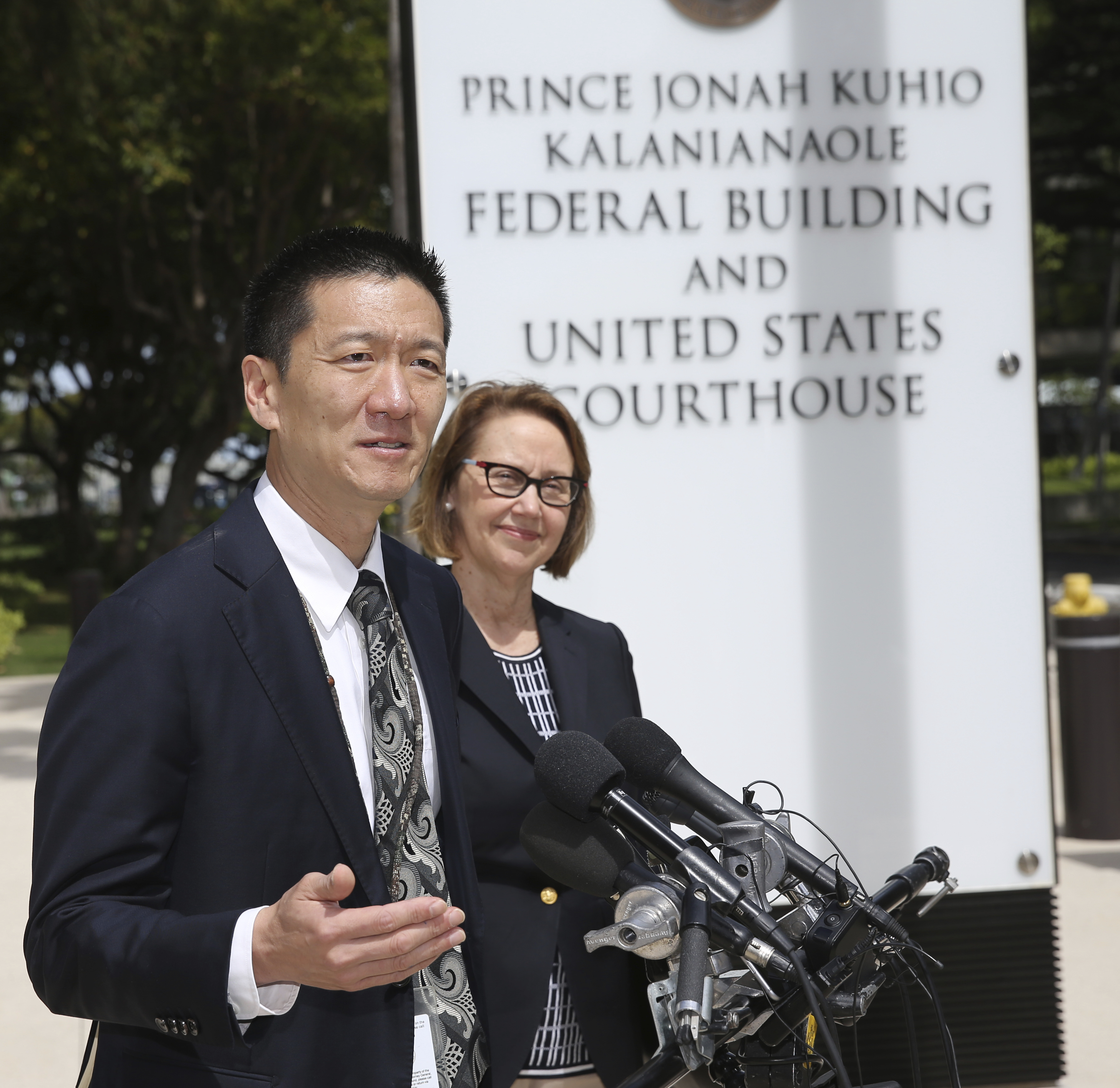 Hawaii Attorney General Douglas Chin, left, and Oregon Attorney General Ellen Rosenblum speak at a press conference outside the federal courthouse on Wednesday in Honolulu. Hearings were scheduled Wednesday in Maryland, Washington state and Hawaii on President Donald Trump's travel ban.