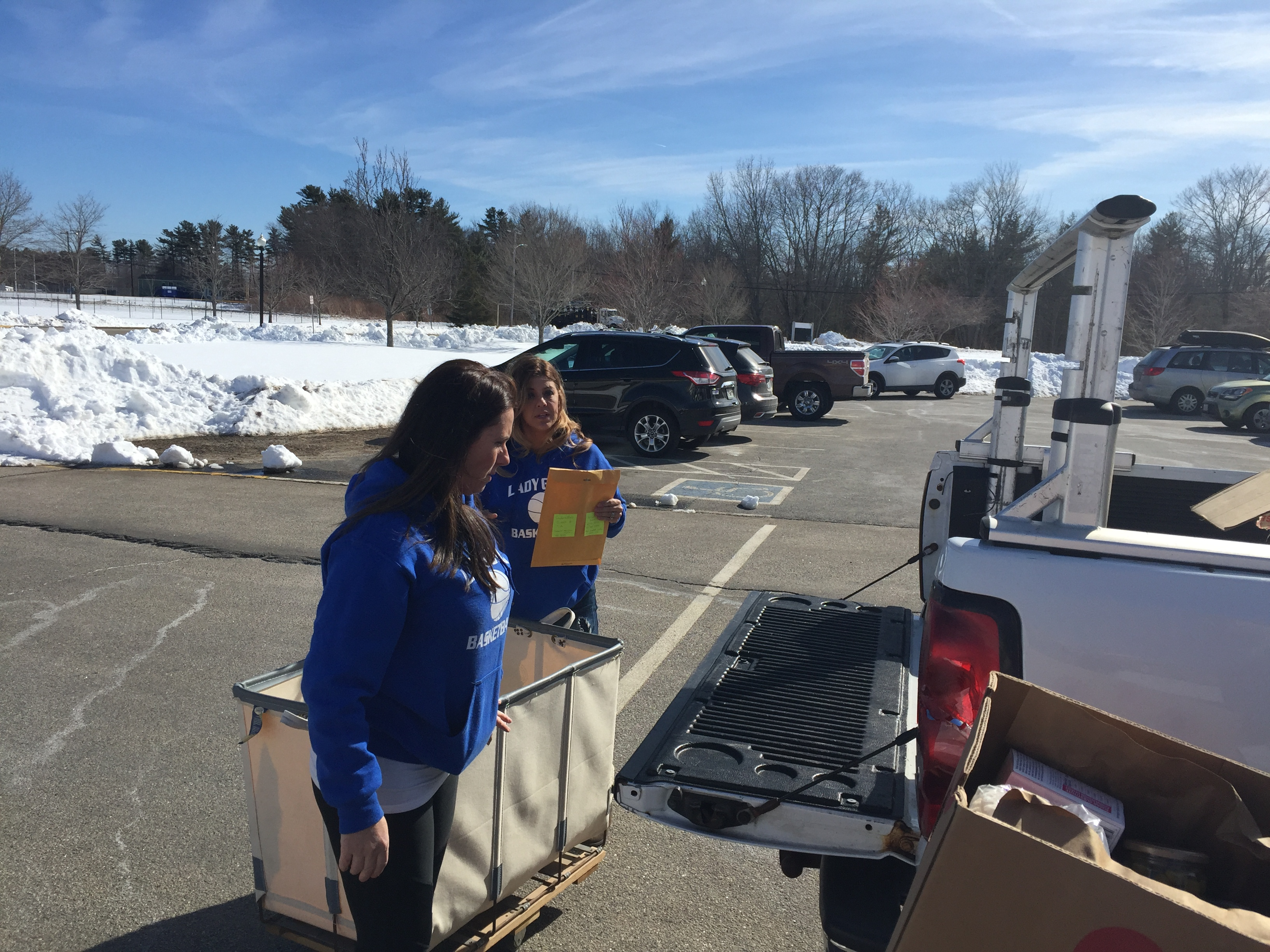Rose Bowdoin and Erica Albair pause while loading donations for the Doucette family in a truck in front of Old Orchard Beach High School Monday afternoon.LIZ GOTTHELF/Journal Tribune
