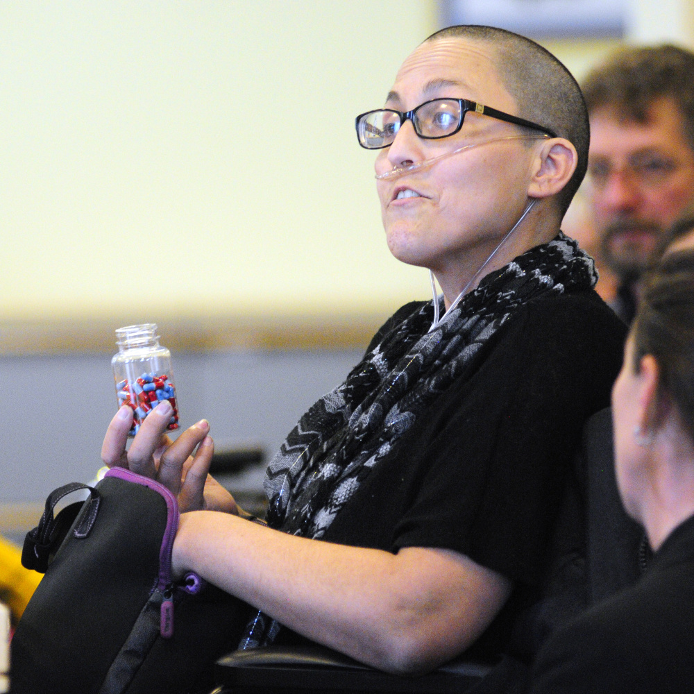 "Stephanie Packer, who is terminally ill, holds pills that she said were prescribed to her as an option for ending her life under California's ""death-with-dignity"" law. Packer, who opposes such laws, said her health insurer would pay for the pills but not for chemother- apy."