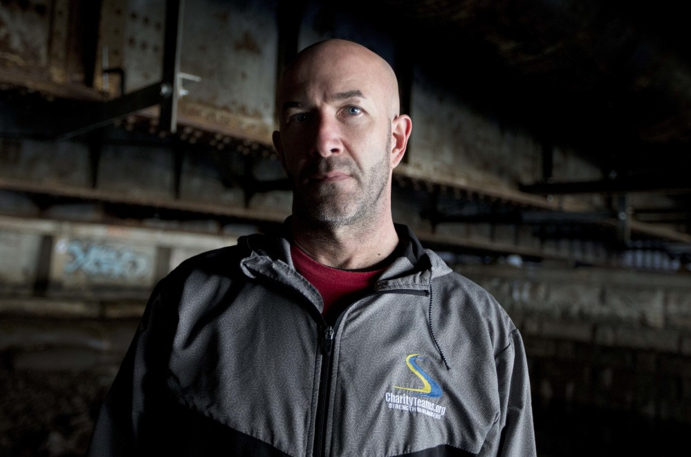 Danny Dwyer poses last month under the bridge where he used to sleep when he was homeless in Boston. Dwyer, 50, plans to run in the Boston Marathon on April 17. It's the latest step away from his former battles with drug addiction, job loss and four years living under the bridge.