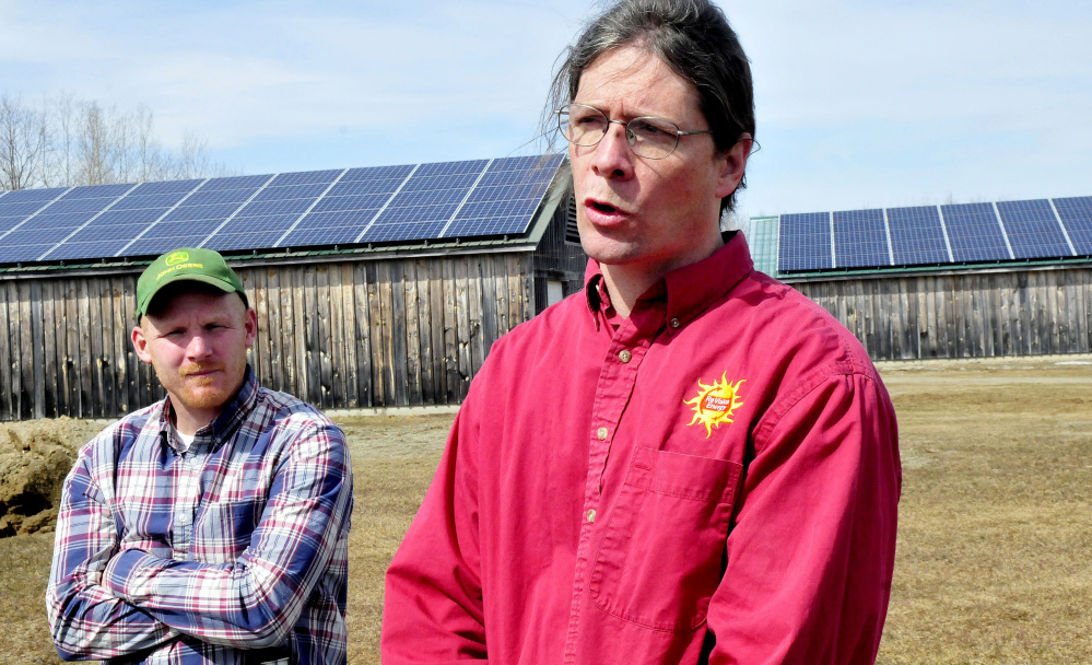 John Luft, right, of ReVision Energy, speaks about the solar system that generates electricity for the Maine Organic Farmers and Gardeners Association in Unity on Monday. At left is MOFGA facilities director Jason Tessier.