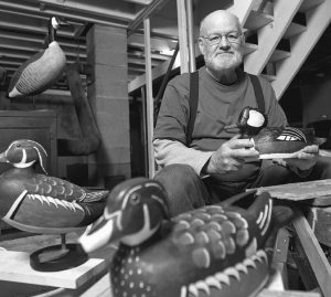 DEAN HURLIMAN holds his favorite carved decoy thus far, a hooded merganser duck, while posing with other carvings he has done over the years in his basement workshop at his home in Burlington, Iowa.
