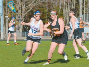 "SHANNON HARTY (12) of the Mt. Ararat High School lacrosse team moves up field with the ball while Holly Black of Brunswick presses during Tuesday's ""Battle of the Bridge"" season opener in Topsham. Jenna Brooks scored five goals as the Dragons cruised to an 8-4 KVAC win under first-year coach Dave Boucher."