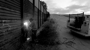 """AA U.S. BORDER PATROL agent working with a border wall repair crew welds a section of steel over a hole cut in the border wall in San Diego. One potential bidder on President Donald Trump's border wall with Mexico wanted to know if the government would help if its workers came under """"hostile attack."""" With bids due today on the first design contracts, companies are preparing for the worst if they get the potentially lucrative but controversial job."""