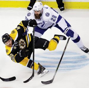 BOSTON BRUINS center David Krejci (46) tumbles to the ice as he is pressured by Tampa Bay Lightning defenseman Luke Witkowski (28) during the first period of an NHL hockey game in Boston on Tuesday. The Bruins won, 4-0, to clinch a playoff spot.