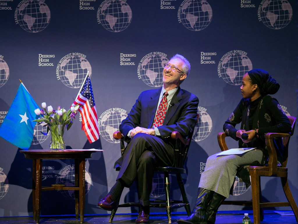 Ambassador Stephen Schwartz thinks about his answer to a question by Deering High School junior Amran Mahamed, right, one of the moderators for Wednesday night's discussion at the school.