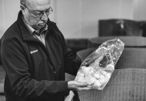 RICK ELLIOTT OF BRISTOL SEAFOOD in Portland examines a bag of scallops at auction in New Bedford, Mass. in this undated photo provided by Christopher Cary. Fair trade certification status is now gaining in prominence with seafood in the U.S., where interest is growing in the story behind the fish and shellfish people consume.
