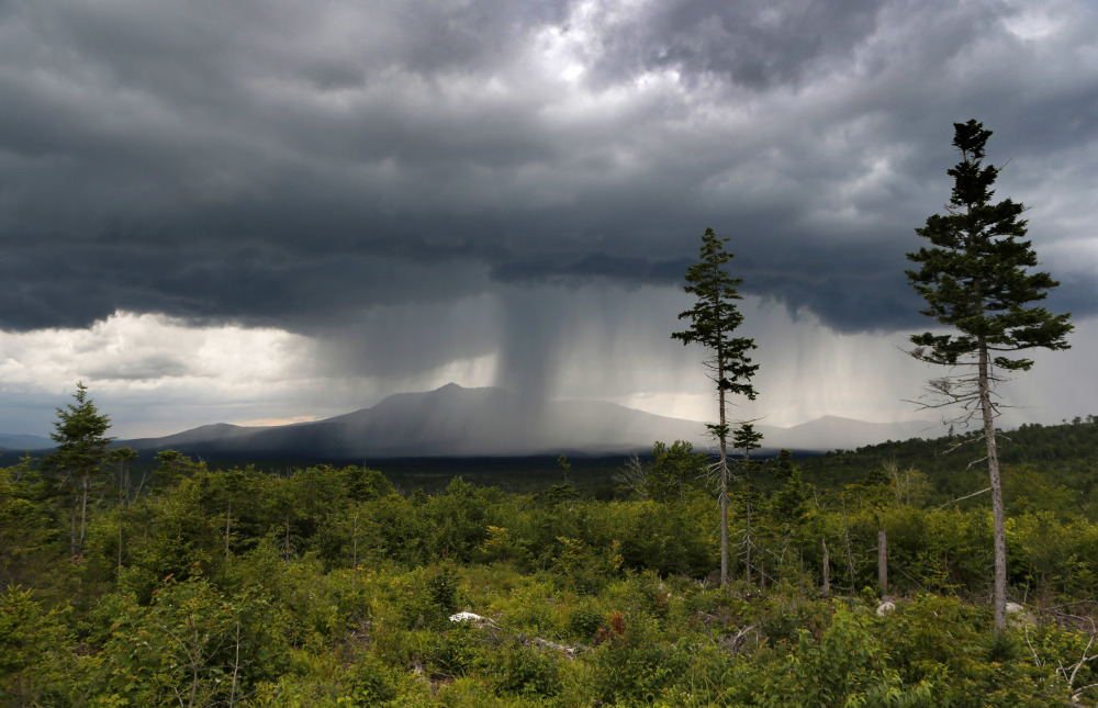 A rainstorm passes over Mount Katahdin in this 2015 view from land that is now the Katahdin Woods and Waters National Monument. Don't expect to see road signs to the monument on Interstate 95, at least not this summer.