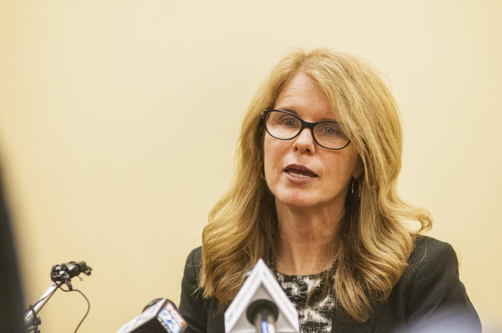 Health and Human Services Commissioner Mary Mayhew reads a statement about her resignation to reporters on May 26 at the department headquarters in Augusta.