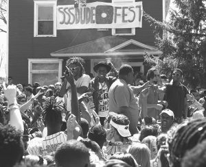 """BRADLEY TAYLOR, owner of Sssdude Nutz, stands center-stage at the """"Sssdude-Fest"""" block party in Dinkytown of Minneapolis."""
