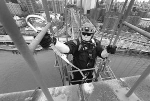 A NEW YORK POLICE EMERGENCY SERVICES UNIT officer hooks a carabiner onto a rail as he reaches the top of the Brooklyn Bridge during a training exercise in New York. Training exercises such as the recent climb up a suspension cable to the top of the iconic bridge, protected only by safety harnesses clipped to a wire, are designed to get team members thinking beyond the risk to their own lives so they can help save someone else's.
