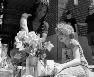 ANGEL SAULS, left, helps her stepdaughter, Coco Douglas arrange a sign and some painted rocks she made for a memorial in Portland, Oregon, on Saturday for two bystanders who were stabbed to death Friday while trying to stop a man who was yelling anti-Muslim slurs and acting aggressively toward two young women.
