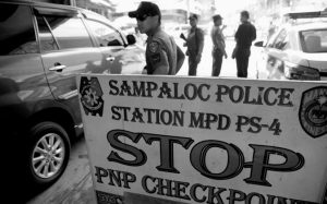 POLICEMEN watch vehicles at a checkpoint in Manila, Philippines, today as the Philippine National Police is placed under full alert status following the declaration of martial law in Mindanao.